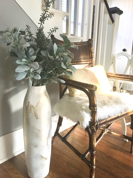 large white vase, about three feet high, painted white the painted over in spots with gold.